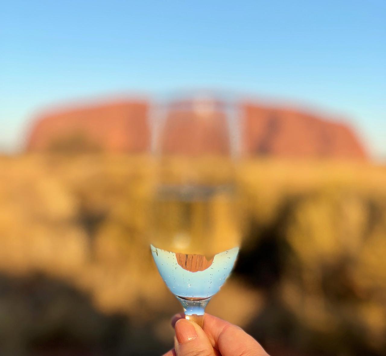 画像: ウルルに到着!スパークリングワインを片手に「乾杯!」グラスに映る「逆さエアーズロック」で記念撮影です♪