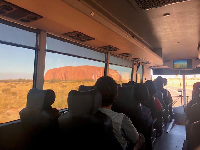 画像: 到着後はウルルの観光へ!バス車窓からだんだんと大きくなるエアーズロック(ウルル)へ向かいます