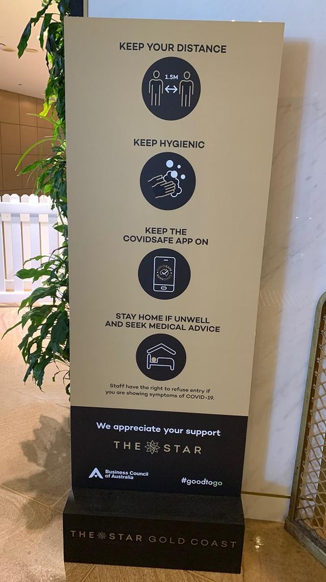 画像: ゴールドコースト「ソーシャルディスタンス/消毒/コロナウィルス対策アプリ導入の推奨/体調不良時について」の看板。(7月下旬 現地スタッフ撮影)