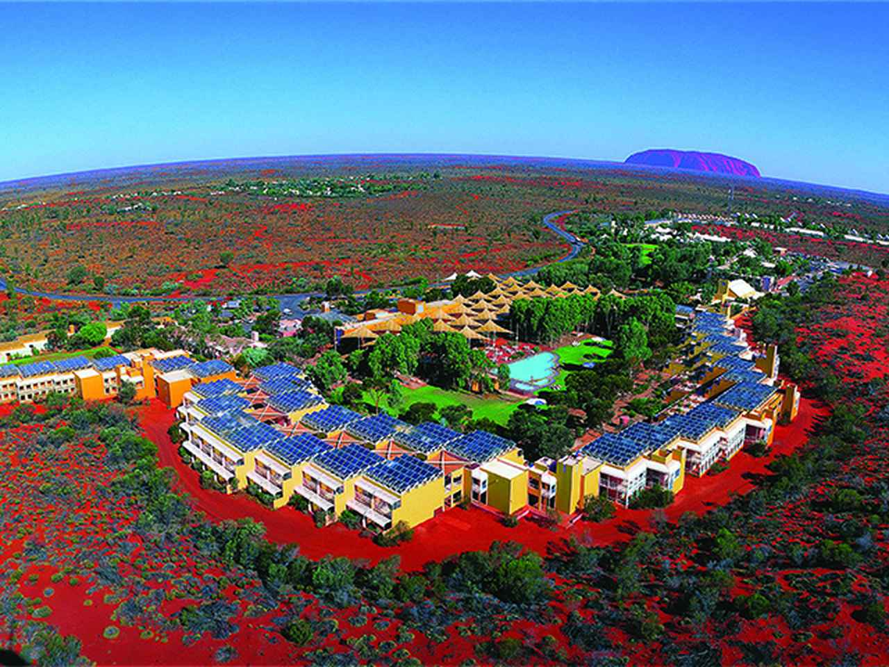 画像: エアーズロックリゾート空撮 ©Voyages Indigenous Tourism Australia ホテルは平家も多くあるが最大でも3階建。景観を遮らないよう丘の高さ以上の建物は建てられない。ちなみに、この画像の中にスタッフの住宅はうつっておりません。(数ヶ所ある中で1ヶ所は、画像の左側の方にあります。あと数cmくらい映る広角ショットでしたら入っていました(笑)。いや、あえて映らないようにしてるのですかね)