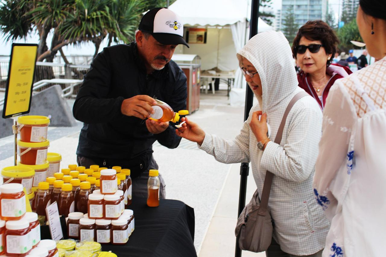 画像: 海沿いのマーケットにてはちみつの試食