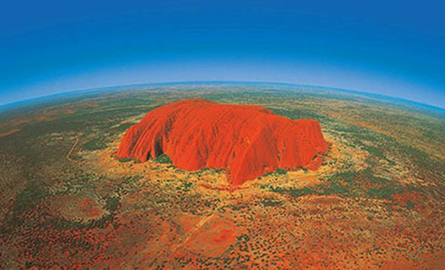 画像: 赤土の大地にそびえ立つエアーズロック、周りには何もない(イメージ) 日本から約10時間かけオーストラリア主要都市で乗り継ぎ、国内線に乗り換え3時間かかってようやく辿り着く僻地。