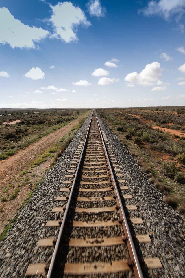 画像: 見渡す限り大平原の中をまっすぐ伸びる線路(©️Journey Beyond)
