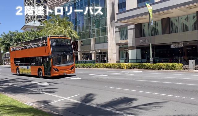 画像: カラカウア通りの観光トロリーバス(乗車率は半分程)
