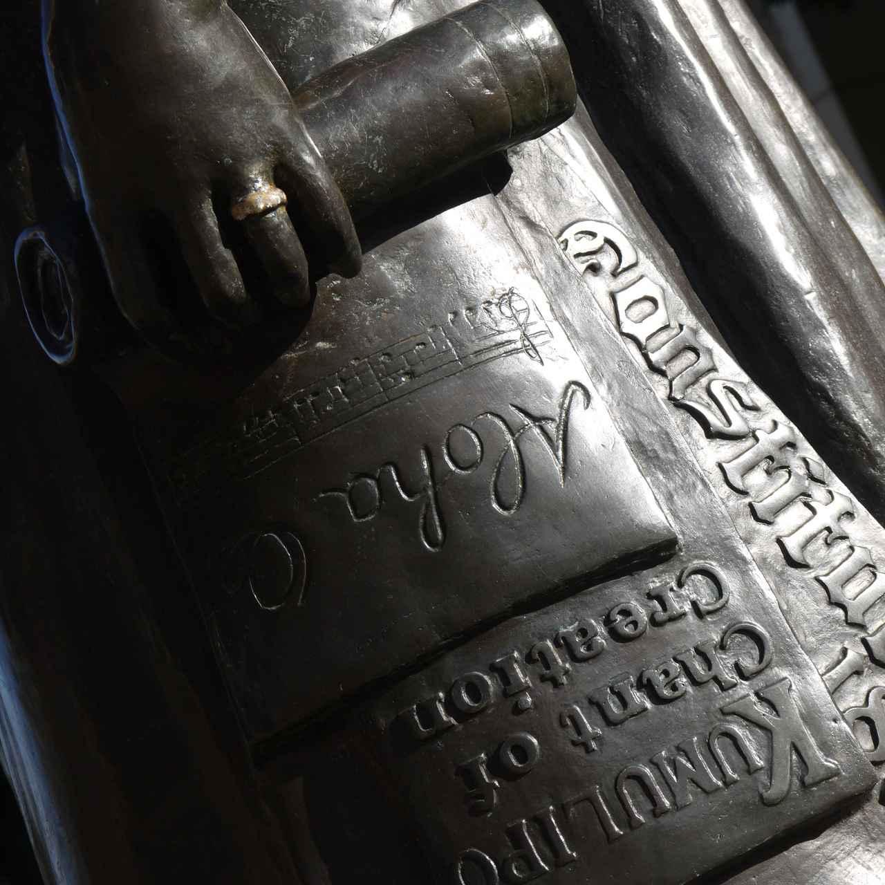 画像: 像が手にしているのは「アロハ・オエ」の楽譜、「クムリポ」の原稿、「新憲法の草案」です