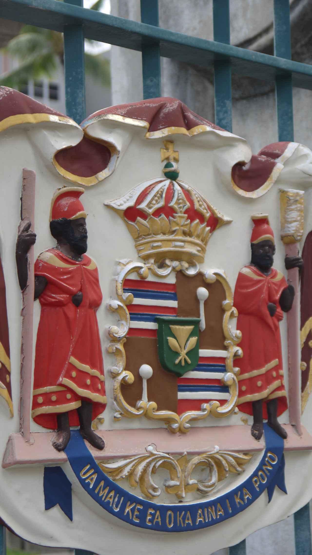 画像: ハワイ王国紋章 カメハメハ大王の双子の叔父、右がカメエイアモク左がカマナワ ハワイ王国のモットー UA MAU KE EA O KA AINA I KA PONOは「土地の統治権は正義によって護られる」という意味(撮影:YUKO)