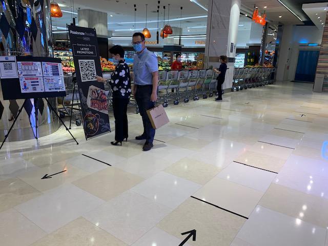画像: ~スーパー入口では入場制限を取り、ソーシャルディスタンスを取る為、床に赤いテープで区切って対応。入口では再度QRコードを読み取り、個人情報の入力とアルコール消毒が必要~ 弊社現地スタッフ撮影[7月21日]