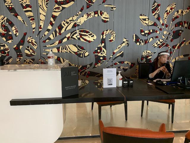 画像: クアラルンプール市内ホテルカウンター スタッフはフェイスシールドを着用しての対応です。 また、お客様が触るペンなどは『消毒前』『消毒後』で使い分けているようです。 弊社現地スタッフ撮影[7月21日]