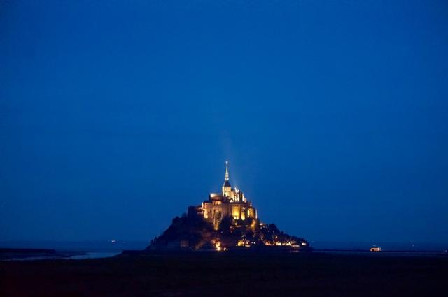 画像: 日没後、ライトアップで輝くモンサンミッシェル