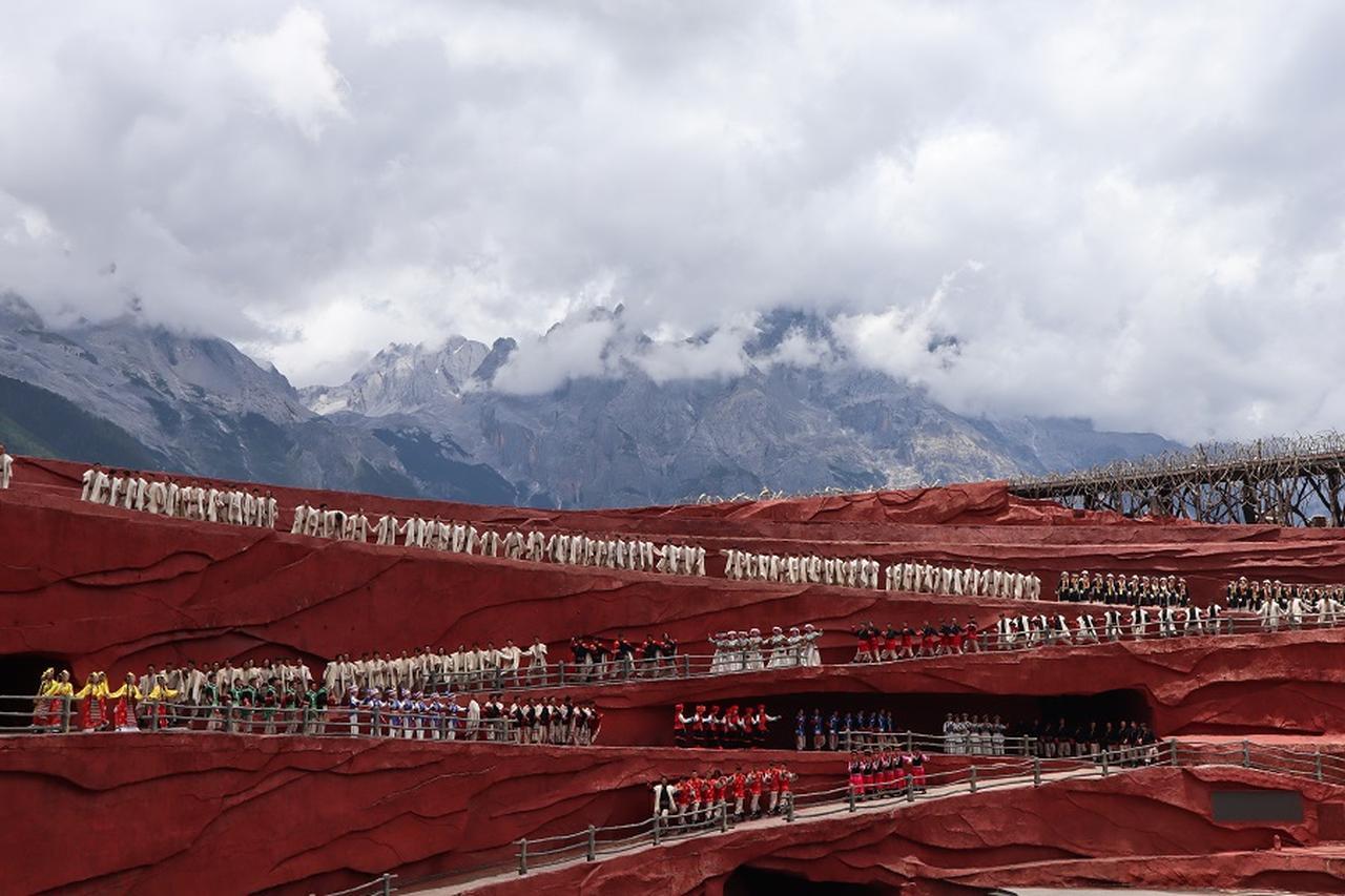 画像: 壮大なスケールの野外劇・印象麗江ショー。ショーの合間に雲の間から玉龍雪山の山頂が姿を現しました。