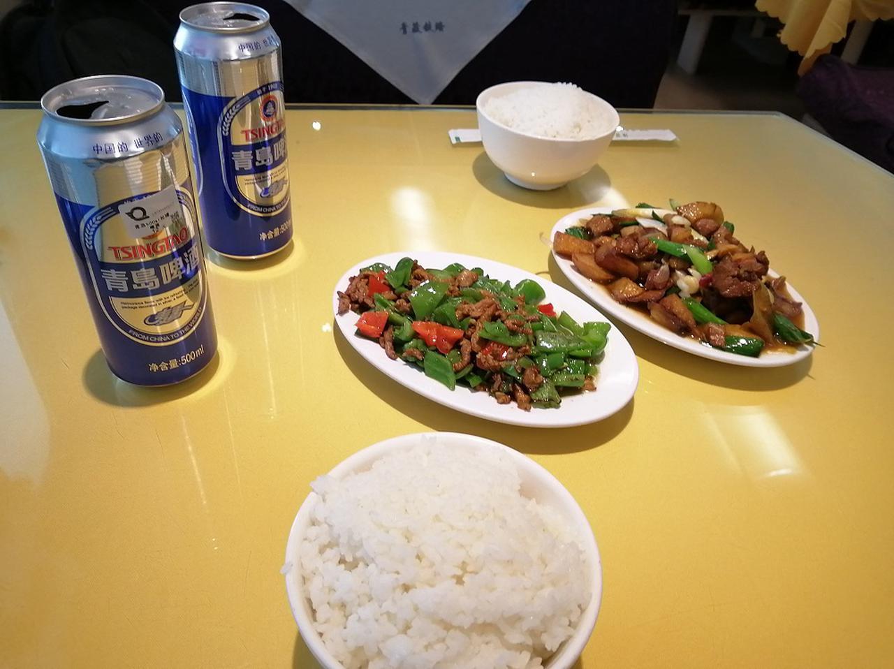 画像: 空いた食堂車にて青椒肉絲とごはんの夕食。左上の青島啤酒(ビール)はこの後筆者を苦しめることになる