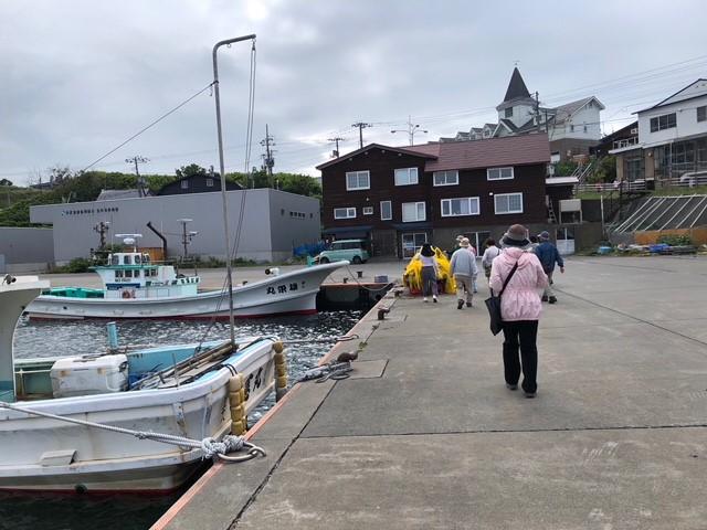 画像: 宿到着後、希望者は地元ガイドの方の案内で、1時間街歩きを行いました。 昔の写真を見ながら、今と比べて見たり、港ではナマコ漁の説明を受けたり♪