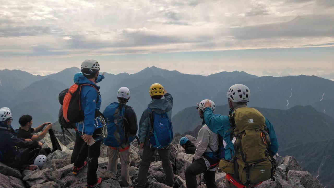 画像: 山頂から来年の目標の鹿島槍ヶ岳を指差す(イメージ)