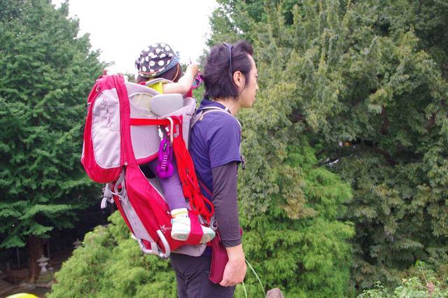 画像: ベビーキャリーを背負ったところ 背面や子どもの足の間に、若干の荷物収納スペースがついています
