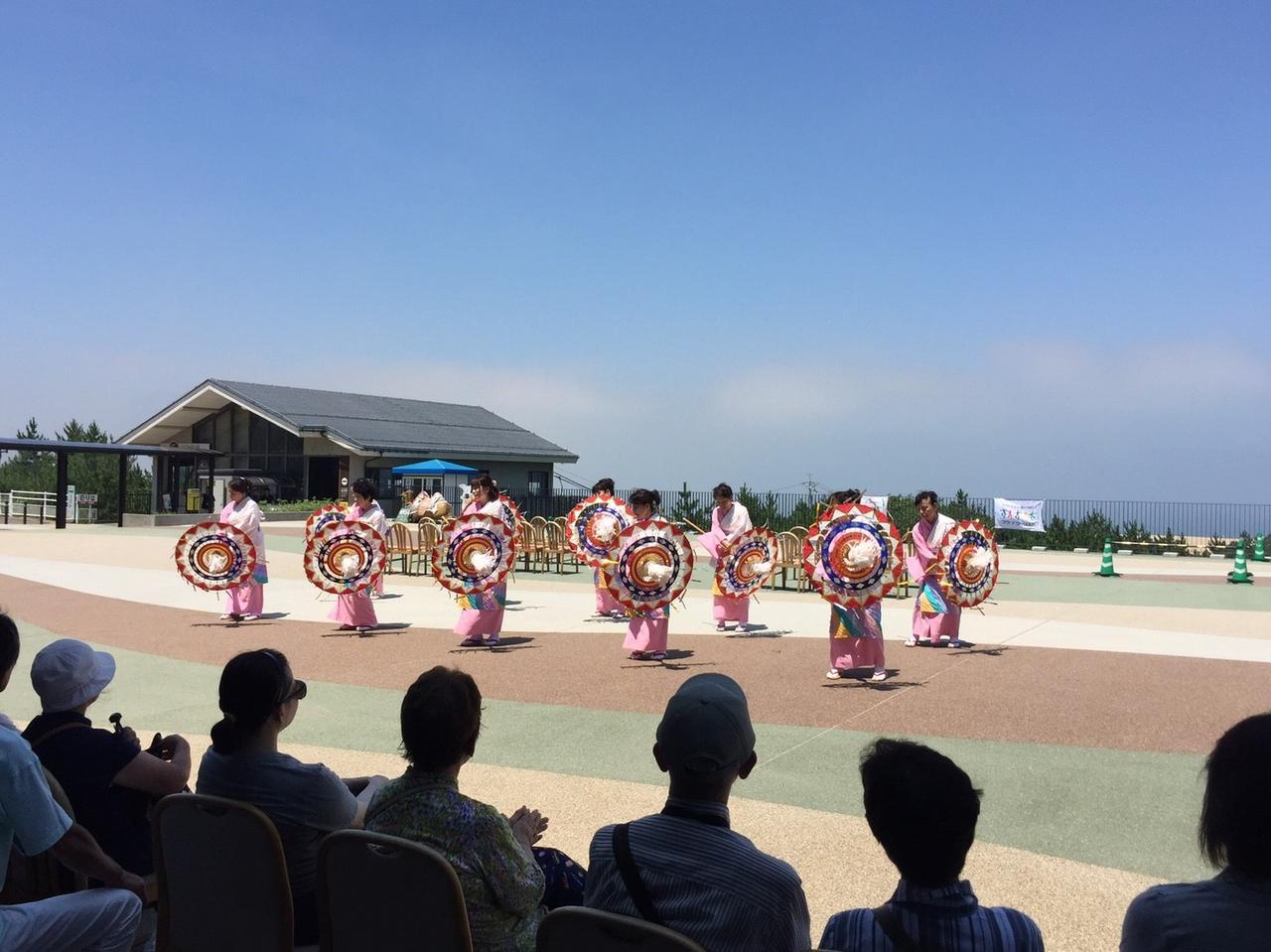 画像: 鳥取砂丘を背景に「砂丘テラス」にて行われた鳥取市観光協会連による「しゃんしゃん傘踊り」の様子
