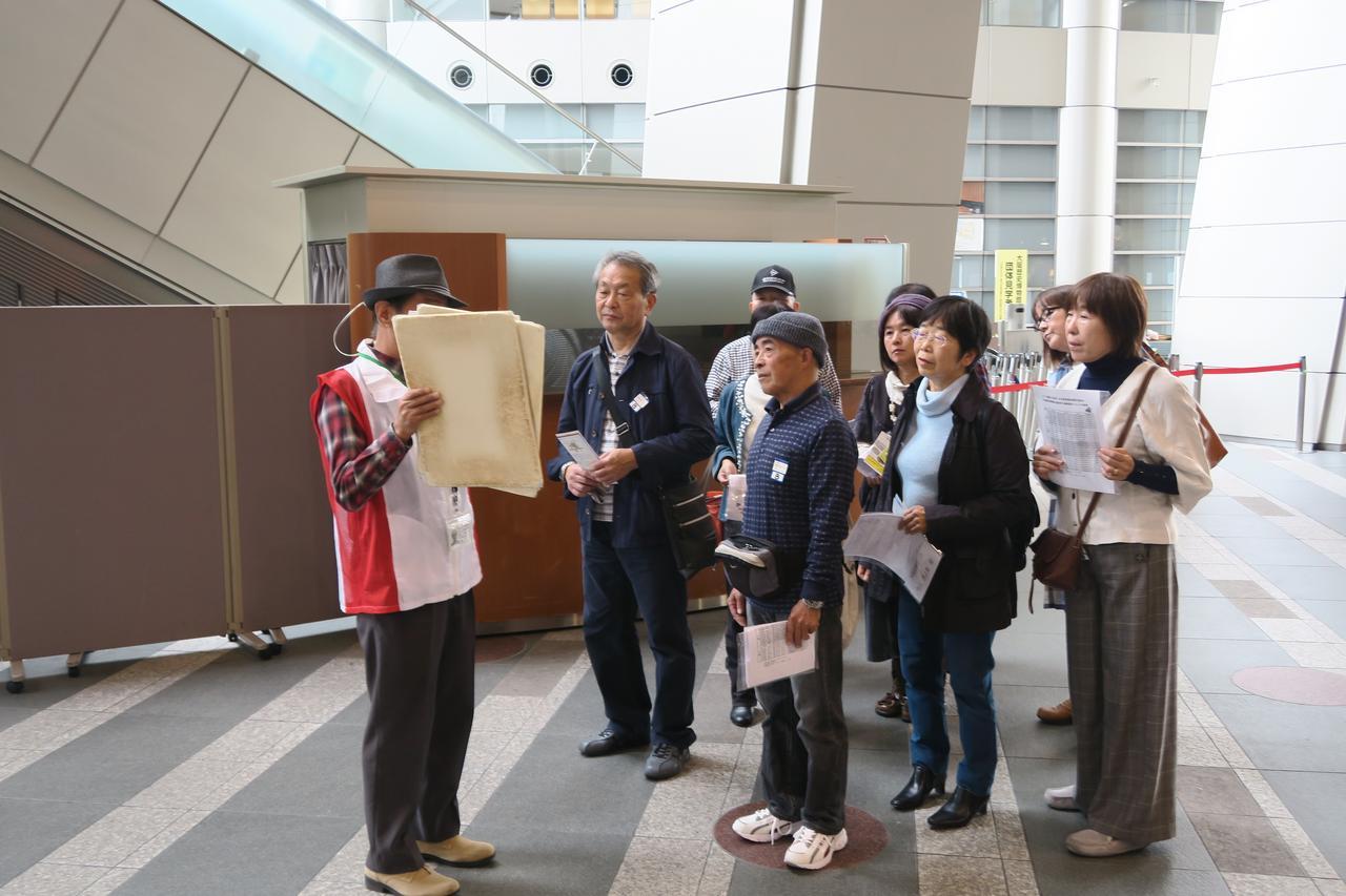 画像: ボランティアガイドさんの案内で難波宮の遺跡について説明を受けるエコースタッフさん
