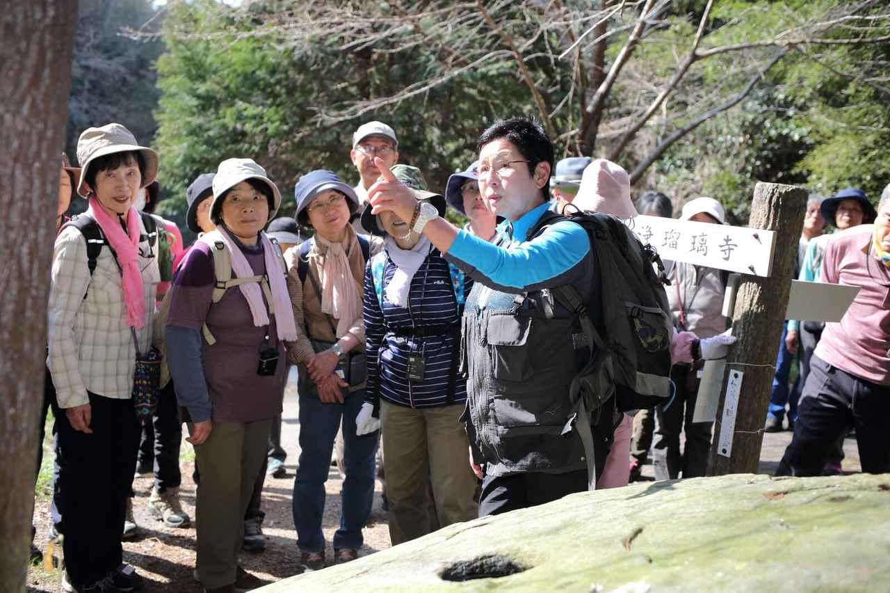 画像: 岩の中央に穴が掘られた「唐臼の壺」にて北尻ガイドの解説に耳を傾ける旅仲間