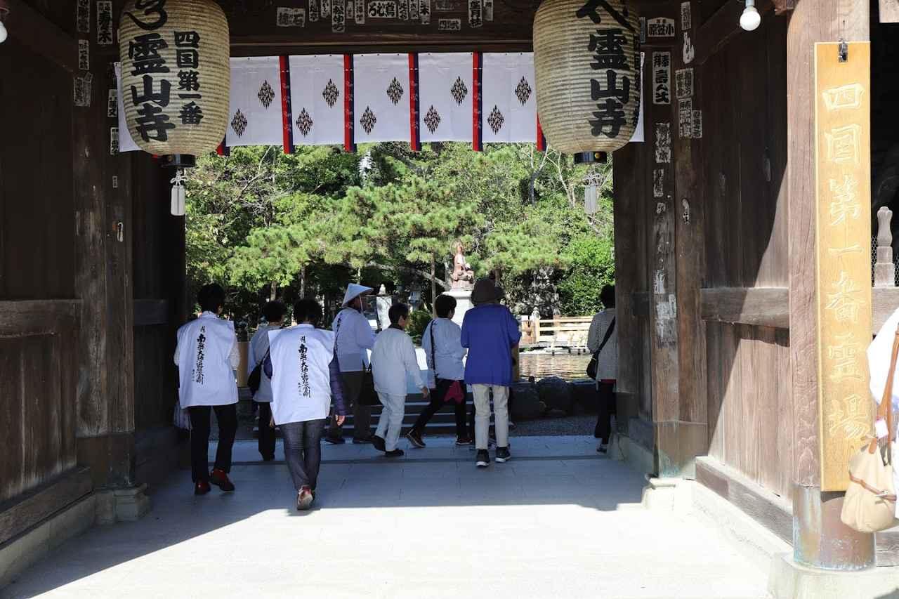 画像: 第1番札所・竺和山霊山寺の山門をくぐる旅仲間たち