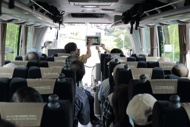 画像: バスの車内。最前列の席にて旧竹林院での撮影アドバイスをする竹下講師
