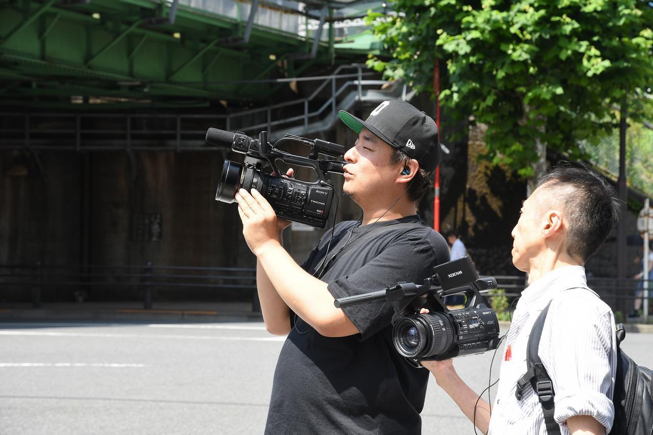 画像: 重いカメラを操る熟練のカメラマン