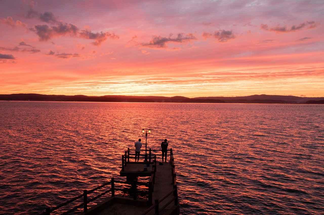 画像: 七尾湾を染める夕日。桟橋では釣りも楽しめるそう