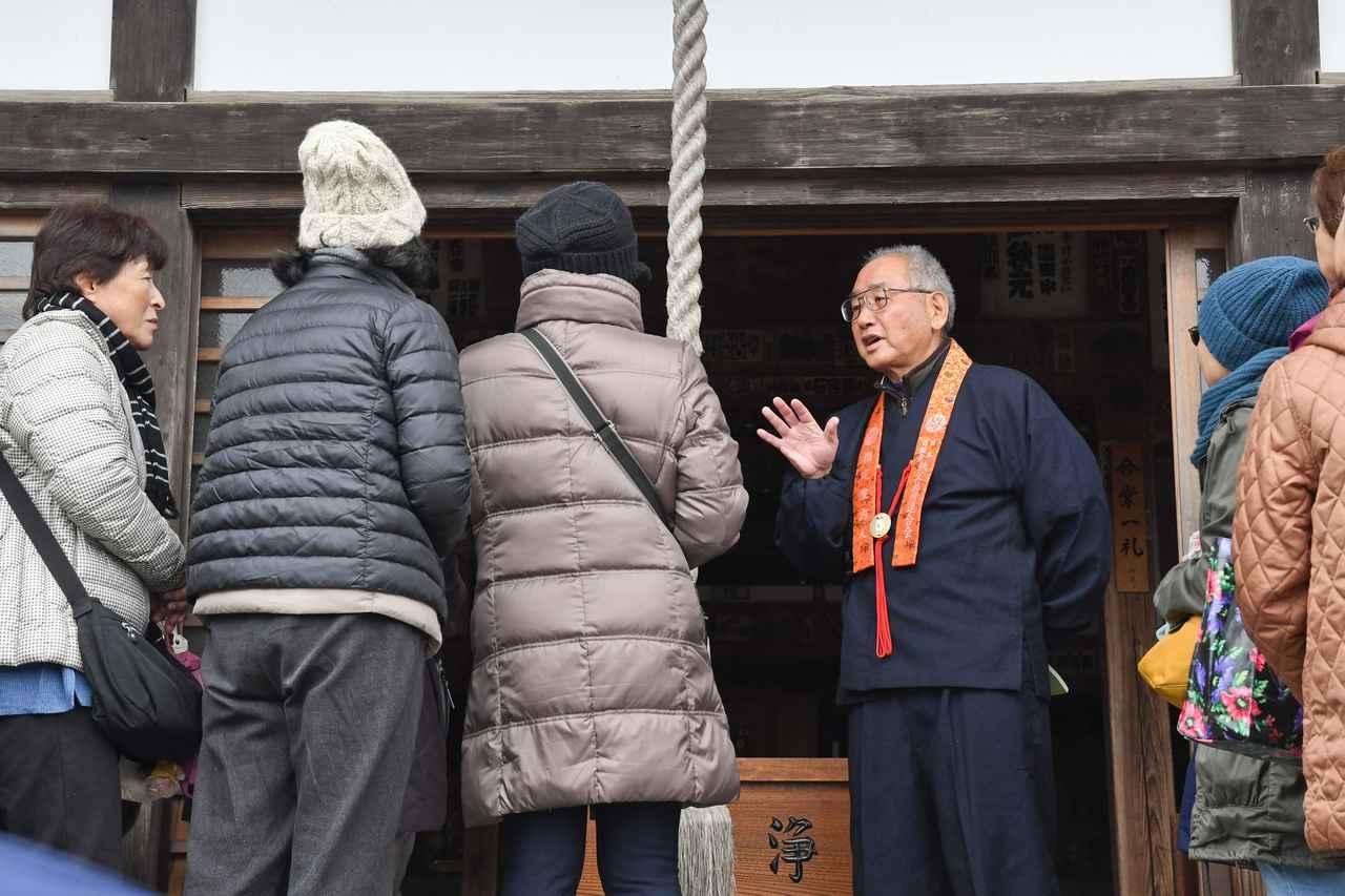 画像: お寺の歴史を解説する、先達の壺内さん。興味深い話で、旅仲間も真剣に聞き入っていました