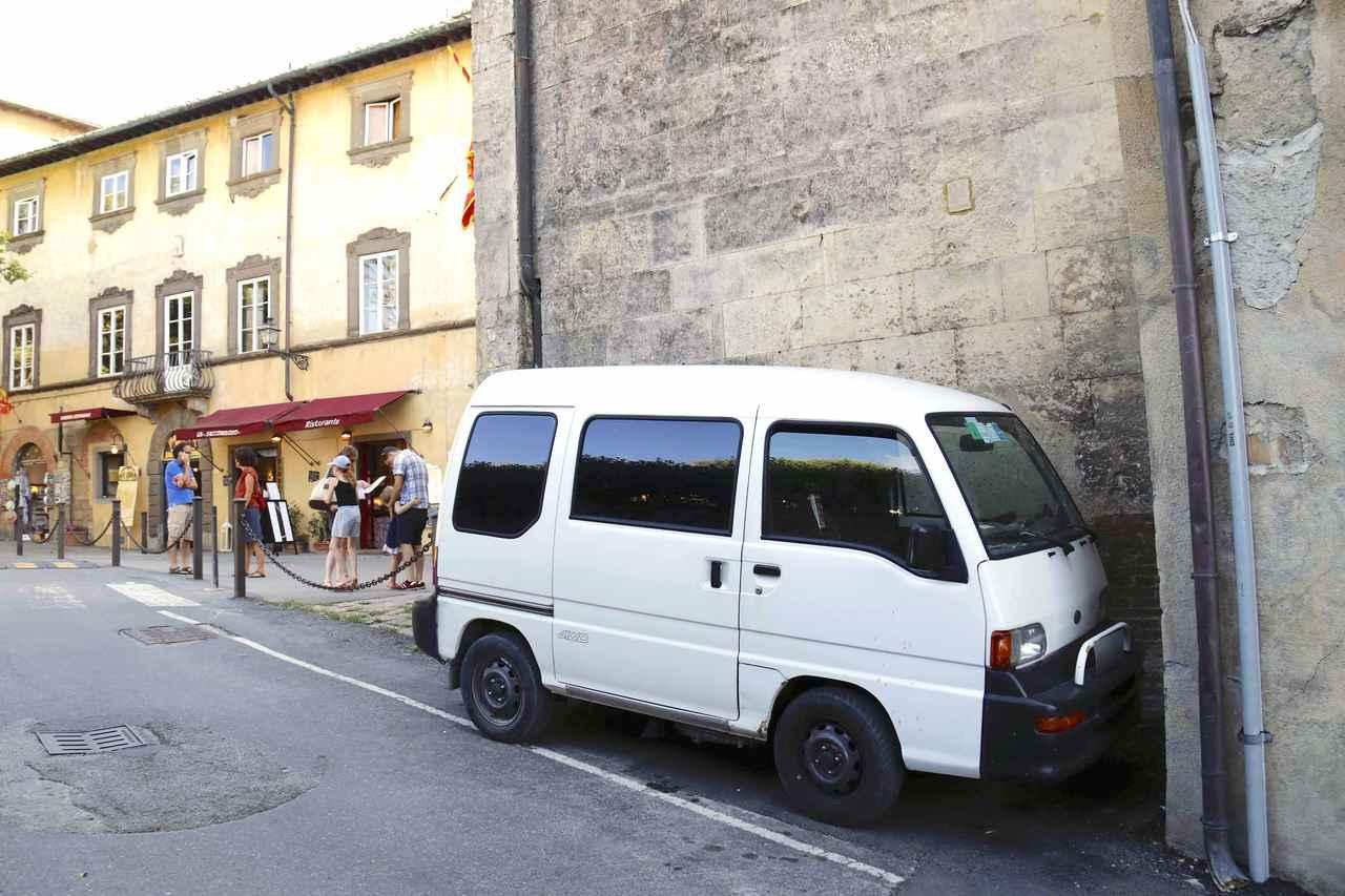 画像: 観光客で賑わう通りの脇道。小さな教会の脇の小さなスペースに、うずくまるように停められていたスバル・サンバー。