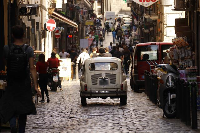 画像: 「フィアット600」がスパッカ・ナポリの雑踏を行く。まるで時間が止まったような風景である。