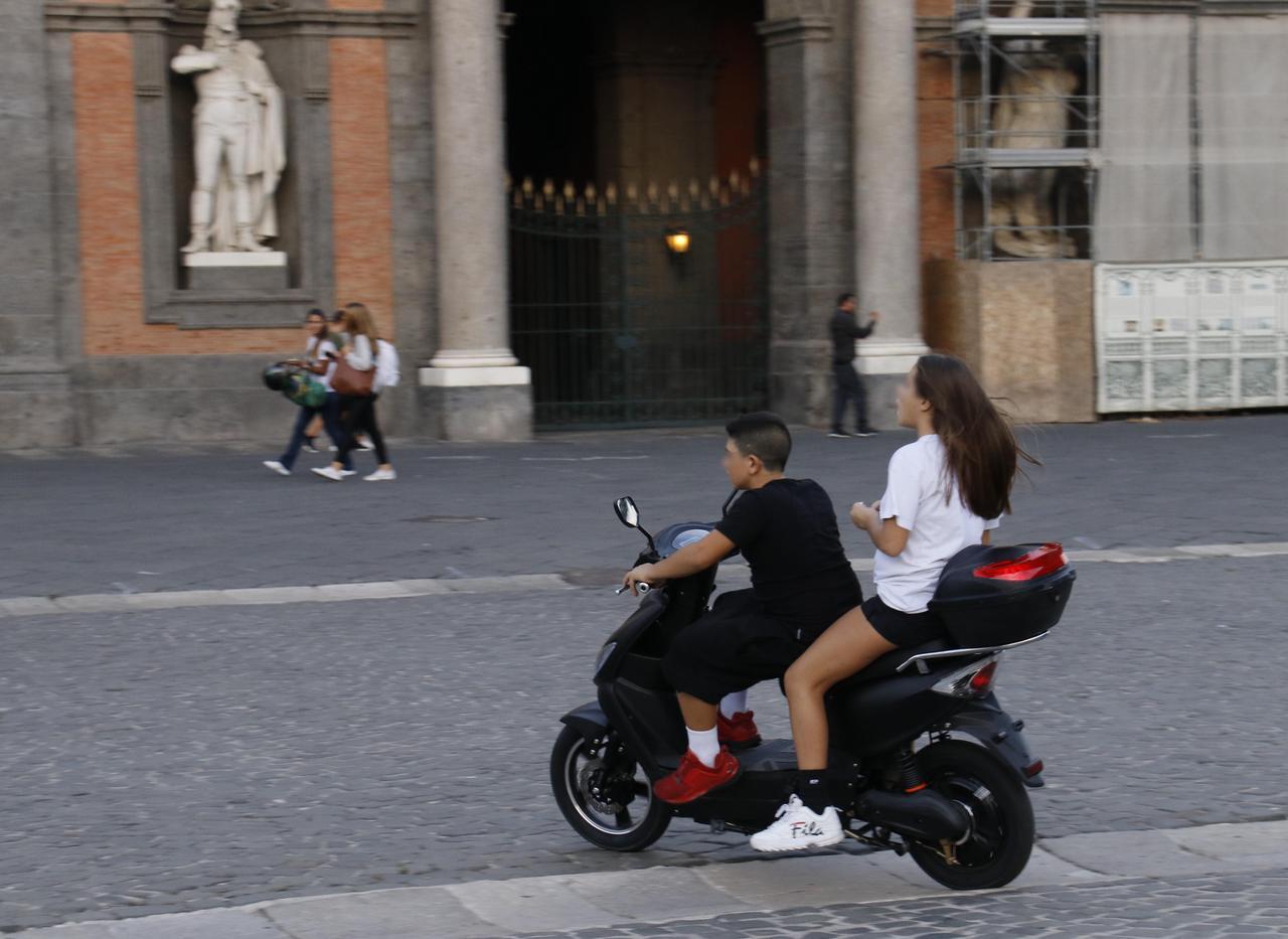 画像: この国では2000年からすべての年齢で原付のヘルメットが義務化されたが、ナポリではいまだ遵守していない若者多し。