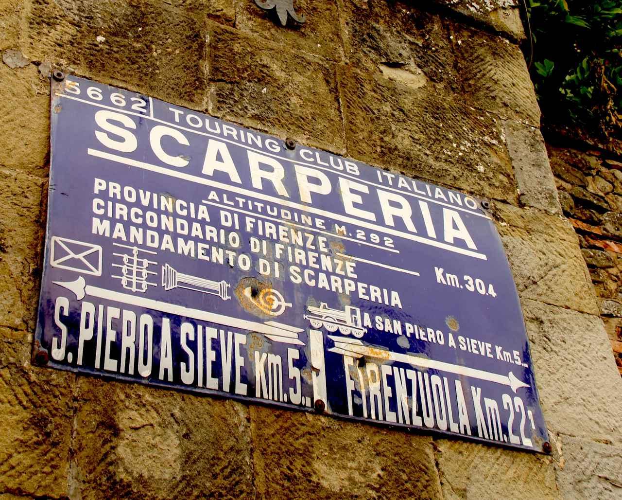 画像: スカルペリーアの町内で。イタリア自動車クラブが20世紀中盤に貼り付けたと思われる道路標識が今も残されていた。