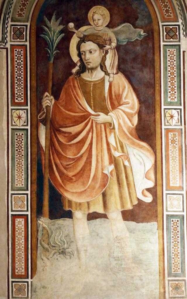画像: スカルペリーアの旧市庁舎入口に描かれた聖クリストフォロス。伝説では、幼いキリストを担いで川を渡ったという。