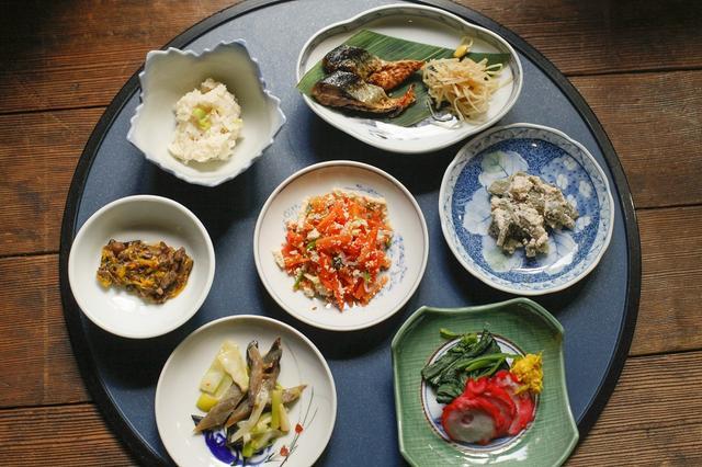 """画像: 「津軽あかつきの会」の""""喜寿の祝い膳""""(一例)から。「一の膳」には、(左上から時計回りに)""""三五八""""に一年間漬けこんだ「にしんの飯寿司」、ふきのとうの茎を使った「ばっけの白和え」、祝い膳の定番「酢だこの三色和え」、津軽らしい酒の肴「身欠きにしんの酢味噌和え」、青唐辛子の漬物「なんば漬け」、サメと大根の酢味噌和え「さめなます」。中央はにんじんとタラコを出汁で炒った「にんじん子和え」"""