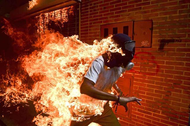 画像: 【スポットニュースの部 単写真】 ロナルド・シュミット(ベネズエラ、AFP通信)2017年5月3日(カラカス・ベネズエラ) ベネズエラのカラカスで、ニコラス・マドゥロ大統領への抗議行動中に機動隊との 激しい衝突が起こり、火だるまになるデモ参加者のホセ・ヴィクター・サラザール・バルザ(28歳) PHOTOGRAPH BY RONALDO SCHEMIDT, AGENCE FRANCE