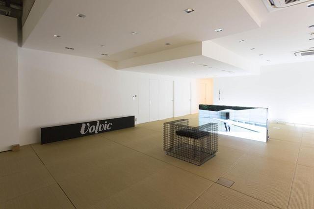 画像: 琉球畳が敷き詰めれらた居間のような空間に映像や企業ロゴを使った作品が配置されている PHOTOGRAPH BY KOICHIRO MATSUI