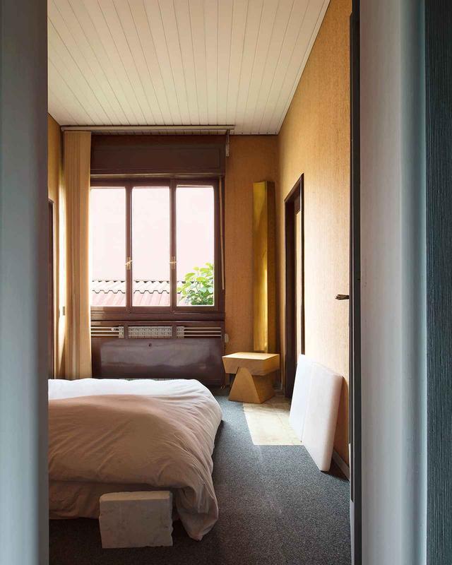 画像: 僧院のように簡素なトニョンの寝室からは、ガレージ区画のひとつの金属屋根とイチジクの木の枝が見える