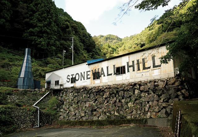 画像: 第二生産工場の正式名は「KAMIKATZ STONEWALL HILL CRAFT & SCIENCE」。サイエンスという名のとおり、旧製材所をリノベした右の建物にはビール酵母培養ラボも内包。石を積み上げた壁にならい、藍染めのウッドパネルを組み上げたAssemble Studioによるテイス ティングサロンは、左のボトル状の建築。樽から仕込むビールの味をゲストと決めるための場だ