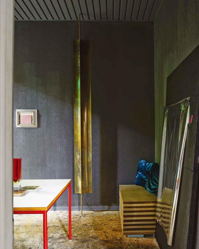 画像: 工業用のフェルトを積み重ねてつくった長椅子の隣には、トニョンがデザインした照明器具が置かれている