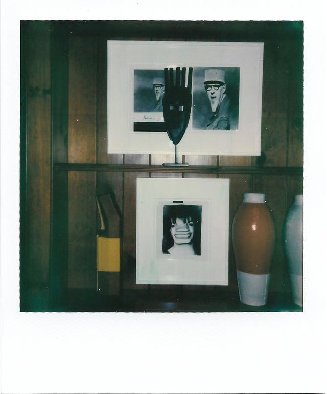 画像: 「節だらけのアルダー材を張ったリビングの長い壁に作りつけられた、本を置くための小さな飾り棚のひとつ。アフリカのお面と、写真家のウィージーが撮ったシャルル・ド・ゴールの写真、それにライザミネリの写真やヘラ・ヨンゲリウスとサイモン・ハッサンがつくった花瓶を組み合わせて戦わせているんだ」