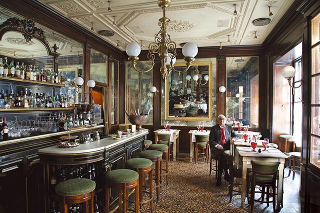画像: 「ジャコモ・ビストロ」のバー・スペースに座っているジャコモ・ブレリ この店は2007年にスタジオ・ペレガリのデザインで建てられた。木枠に縁取られた大きな鏡と幾何学的なセメントのタイル、フランス式のシャンデリアが特徴で、左にあるナポレオン3世風のキャビネットはカウンターになっている