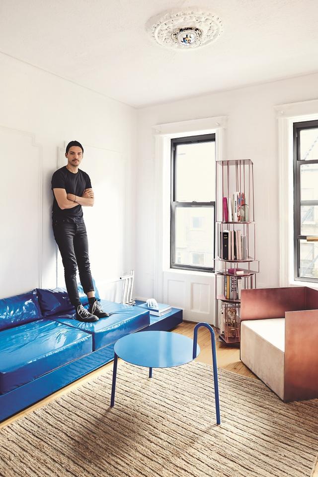 画像: 自作のビニールとコットンのソファの上に立つヌレエフ。いずれも、NYブルックリンのウィリアムズバーグにある自分のアパートのために作った家具だ。鉄製のコーヒーテーブル「1 on 2」は、新しい家具シリーズからの作品