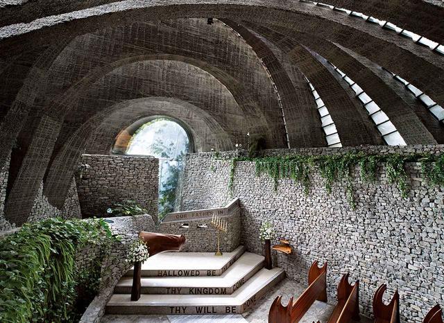 画像: コンクリートのアーチがドミノ倒しのように傾いて連なり、垂直なアーチはひとつもない。中に入ると石を積み上げた壁で囲まれた荘厳な世界が広がる