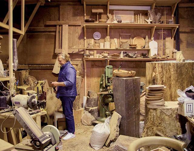 画像: 東京、世田谷の材木店の中にある吉川のアトリエ。小さなスプーンから巨大な木の幹を活かした椅子まで 吉川の作品はさまざま。自身も木工作りをやるスティーブンは木の種類を聞いては感触を確かめたり、匂いを嗅いだり