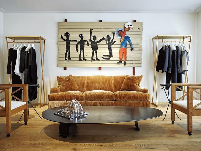 画像: 世界最大の店は、今やラップトップの中にある。小売業における最新のコンセプトは、親密さと家にいるような居心地のよさだ。写真は「ザ ロウ」 のニューヨークにあるタウンハウスの店舗。バスキアの作品がジャケットの隣に並ぶ PHOTOGRAPH BY MICHAEL ROCK