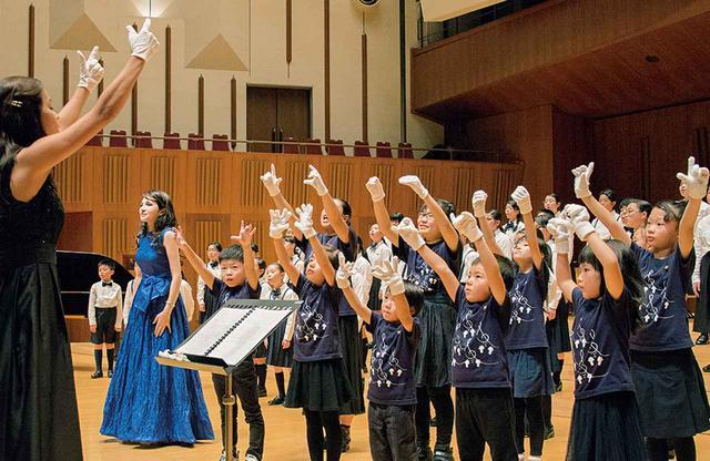 画像: 本番直前、ゲネプロ中の東京ホワイトハンドコーラスの子どもたち。指揮をするマク先生は公演のためにベネズエラから来日したばかり。でも、いつもビデオで一緒におけいこをしてきたから息はぴったり