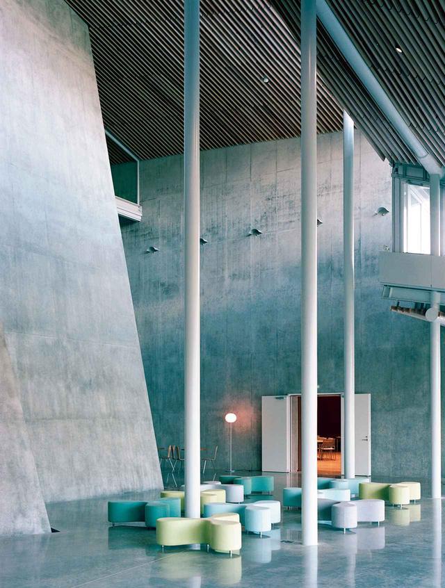 画像: 「荘銀タクト鶴岡」内部。大ホールを囲む通路沿いには、小ホールや練習室などを配置。通路にも、SANAAデザインのソファや椅子が置かれ、ゆったり過ごせるよう配慮されている。天井はSANAAでは珍しく木のルーバーを設置。鶴岡市の木材を使用している