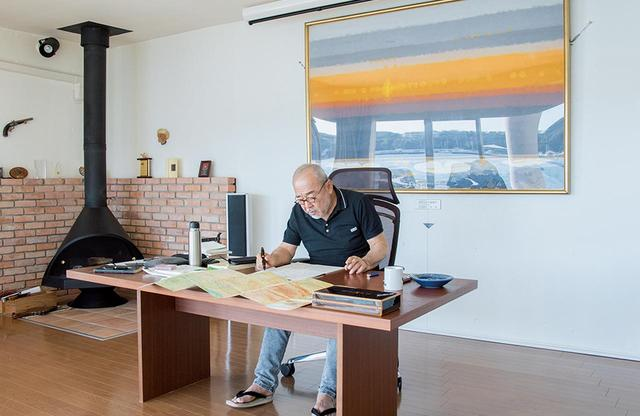 画像: 別荘ではこの大テーブルで執筆。背後の油絵は母方の叔父、森通の作品で、サハラ砂漠の夜明けを描いたもの。 執筆中はオランダのシガリロZinoを、くつろぎのときはキューバ産葉巻をたしなむ