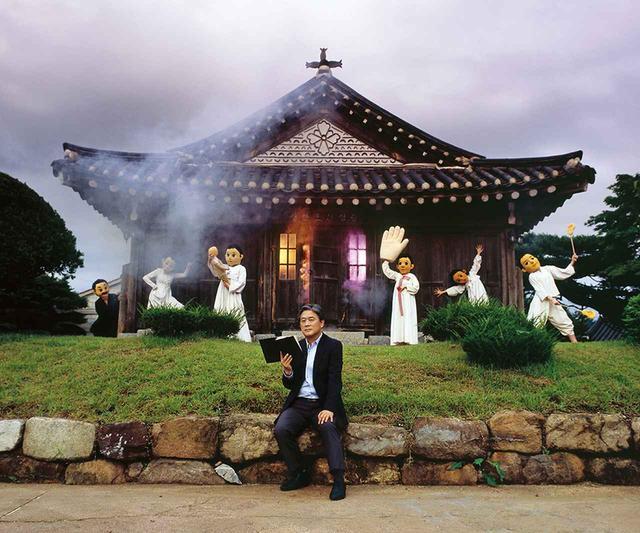 画像: 韓国人写真家のオ・ソックンは、2006年から撮影している巨大な人形の頭をかぶったふたりのモデルの写真シリーズで知られている。人気の子ども向け絵本シリーズのキャラクター、チョルスとヨンヒをモデルにしたものだ。彼らを撮影した写真は、韓国人が子ども時代に経験したトラウマを表現している。こちらのパクのポートレートは、ソウルから約1 時間ほどの江華島にある江華聖堂の前で撮影。チョルスとヨンヒに似た人形の頭をかぶったモデルを後ろに配した PRODUCTION: KKOTSBOM. BAT MADE BY KIM SOOHWAN,EXTRAS: BAEK SEUNGKEE, CHOI YOONJAE,LEE HAEIN,LEE JIHYANG, PARK SOJIN, SHIN YEJOO, PHOTO ASSISTANT: KIM HONGHEE