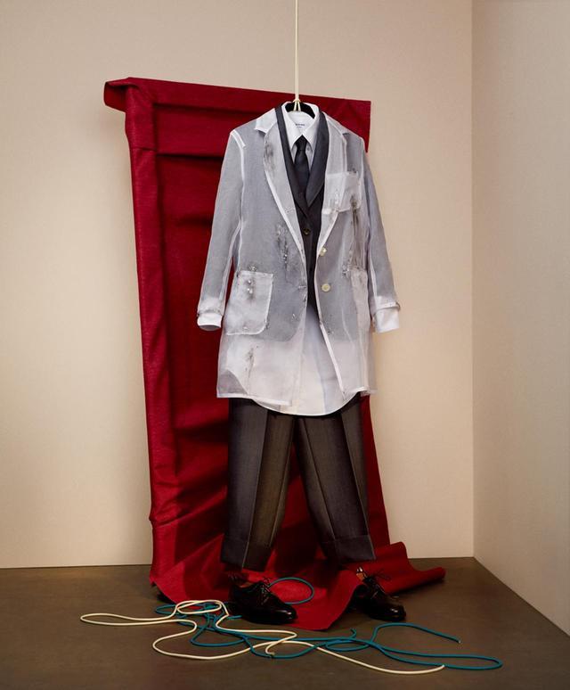画像: ブラウンは、抽象表現主義の先駆者マーティンのために、伝統的なサックスーツ(上着がゆったりしたスーツ)というクラシックなアイテムを選んだ。ブラウンとマーティンのクリエーションに共通するのは、シンプルさと、派手な色が苦手な点。「僕とアグネスは厳格なところが似ているかな」とブラウン。「この気質をワークウェアに表したくて。彼女の理路整然としたところや、アートへの知的なアプローチには僕も感化されているしね」。シアーなコートは、アトリエでスーツが汚れるのを防ぐためのアイテム。履きやすいオックスフォードシューズは、多様なものを観察し、絵を描くために、つねに立ちっぱなしだった彼女のためのチョイスだ