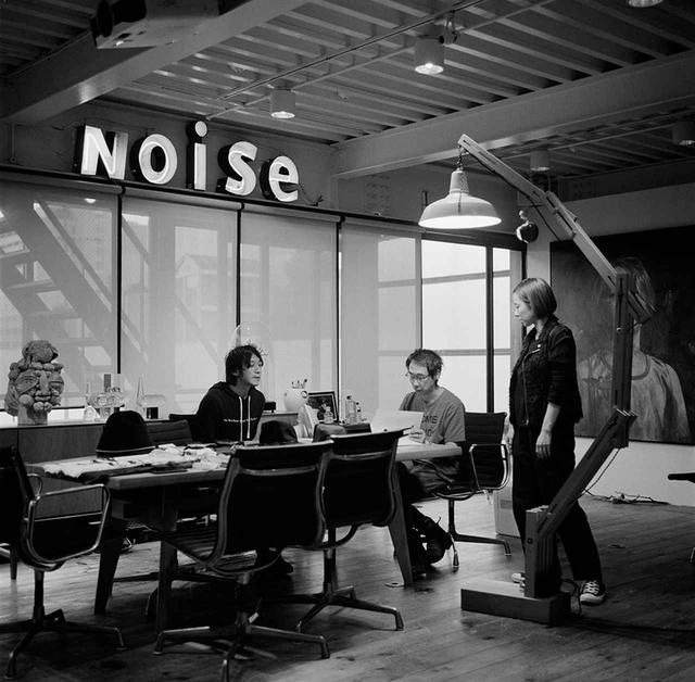 画像: アンダーカバーのコンセプトは『We make noise not clothes(服ではなくノイズを作る)』。高橋のオフィスにある赤と白のネオンサインは、この理想を表したものだ。東京・原宿の裏通りにある、黒い鉄箱が浮いているように見える建物が彼のアトリエだ。最上階は高橋の仕事部屋。そこで高橋はデザインや、できあがった商品の最終チェックを行う。写真は、高橋とメンズラインであるジョンアンダーカバーのデザイナーたちのミーティング風景。高橋の左手側に立つのは、彼の右腕として知られる女性