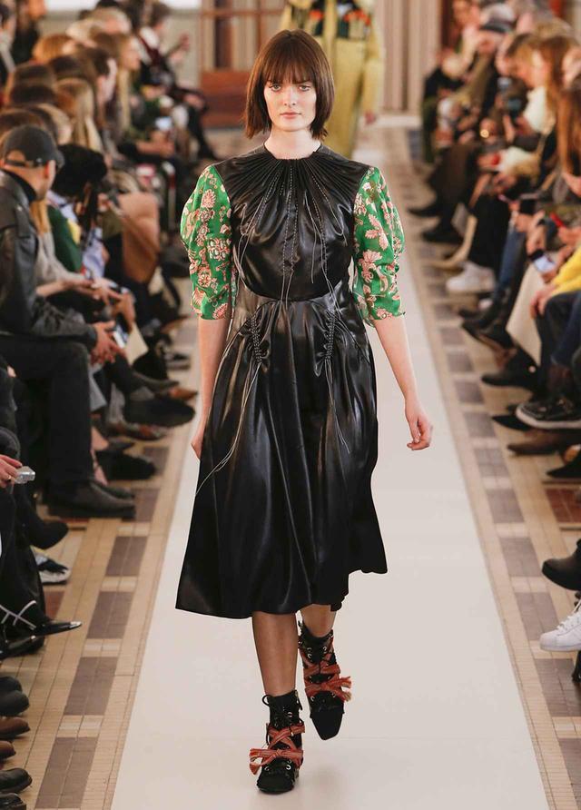画像: 厳格な表情のブラックドレスに遊び心を加える袖の柄は、「祖父母の時代にあったような懐かしさをイメージしています」とセルジュ。シューズは赤いコットンの紐で飾られ、スポーティな表情が加えられている COURTESY OF CARVEN